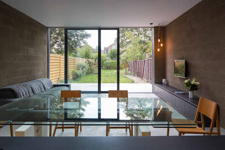 View over dining table with living area and garden beyond Mustard Architects Industrial style dining room