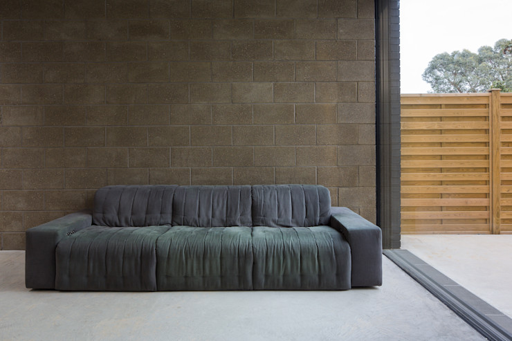 View of exposed block work wall to living area Mustard Architects Industrial style living room