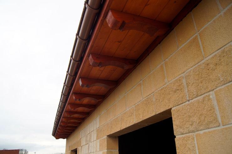 Alero con panel sandwich de madera con núcleo aislante y acabado decorativo en friso abeto barnizado panelestudio. panelestudio Paredes y pisos de estilo mediterráneo