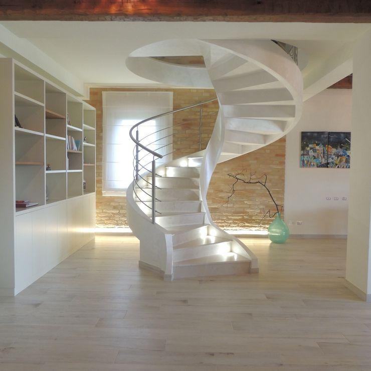 Scala elicoidale moderna in cemento con pedate in marmo e balaustra in acciaio Nadia Moretti Ingresso, Corridoio & Scale in stile moderno