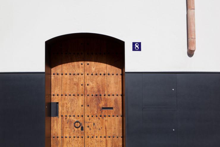 Puerta principal (recuperada, ensamblada para convertirla en corredera) CABRÉ I DÍAZ ARQUITECTES Casas minimalistas