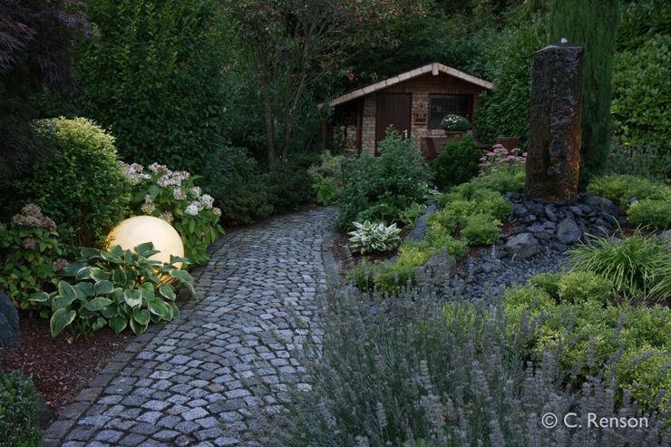 Kamin-Holzlager und Sauna, integriert in den Garten dirlenbach - garten mit stil Garten im Landhausstil