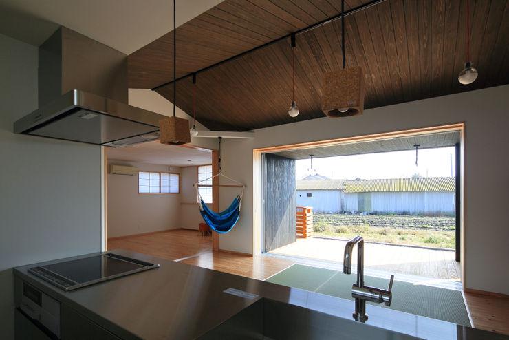 キッチンよりリビング・寝室を見る ㈱ライフ建築設計事務所 ミニマルデザインの リビング 木
