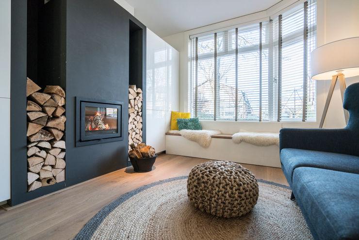 Houtkachel met houtvoorraad bij de erker Masters of Interior Design Moderne woonkamers Hout Grijs