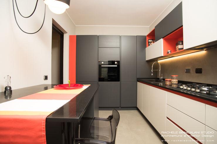 Cucina moderna con pavimento e parete in resina cementizia spatolata colori grigio, rosso, arancio, beige Rachele Biancalani Studio Cucina moderna Grigio