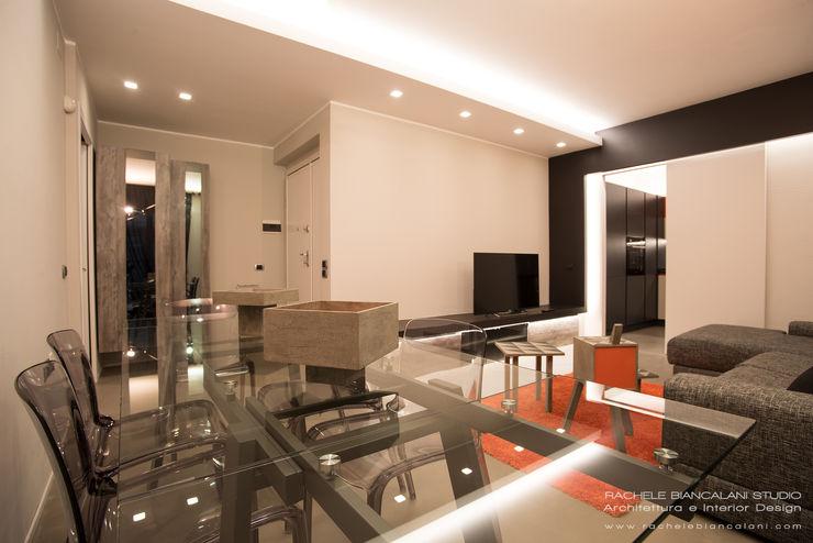 Living con pavimento in resina spatolata, grigio e tavolo in cristallo Rachele Biancalani Studio Soggiorno moderno Grigio