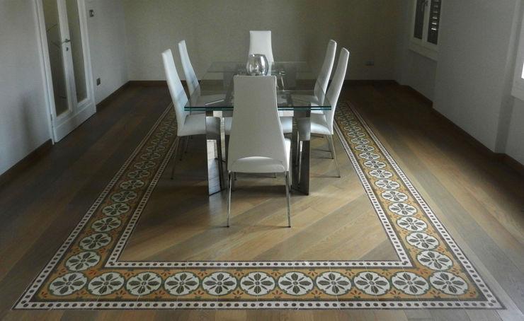 Sala da pranzo: dettaglio del pavimento in legno con il riuso della greca presente nel pavimento in graniglia rimosso GIOIA Biagio ARCHITETTO Sala da pranzo moderna