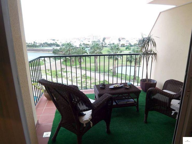 Terraza con vistas al campo de golf homify Balcones y terrazasAccesorios y decoración Ratán/Mimbre Marrón