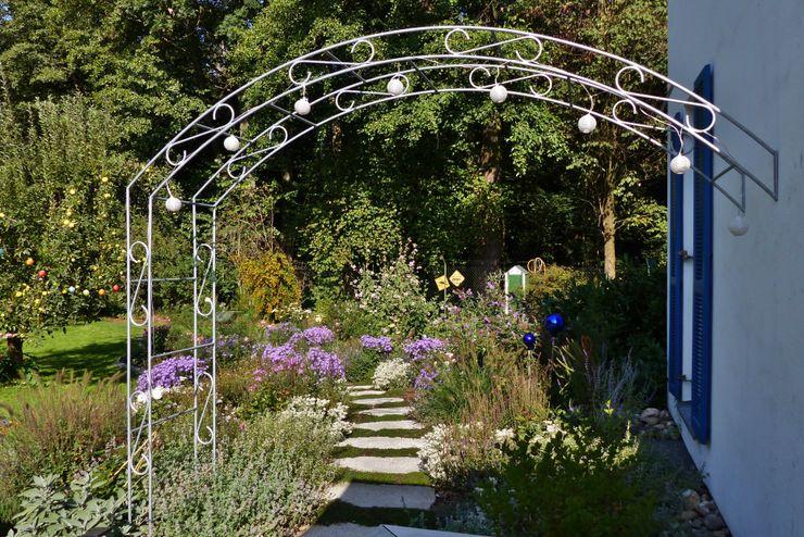durch Rosenbogen an der Terrasse betritt man den Rosengarten KAISER + KAISER - Visionen für Freiräume GbR Garten im Landhausstil