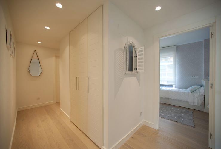 Reforma de vivienda en madera, blanco y tonos azules Sube Interiorismo Pasillos, vestíbulos y escaleras de estilo clásico