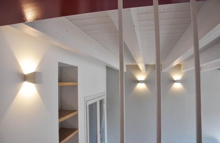 Casa con corte atelier architettura Pareti & Pavimenti in stile moderno