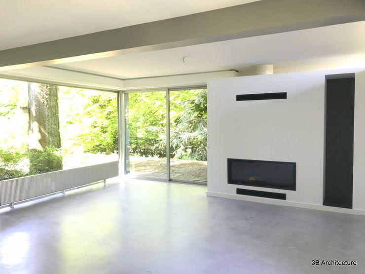La façade du séjour s'anime avec le nouveau volume de la cheminée. 3B Architecture Salon moderne Béton Blanc