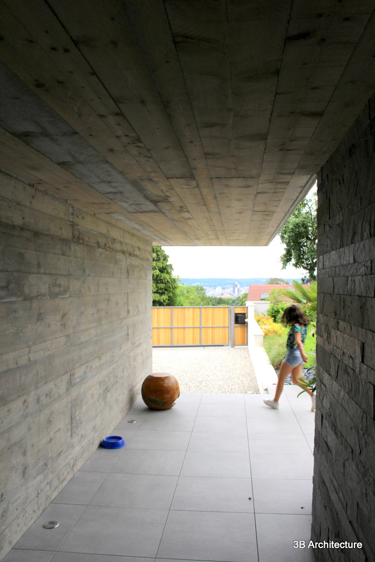 L'entrée se fait à couvert sous un port-à-faux en béton 3B Architecture Murs & Sols minimalistes Béton Gris