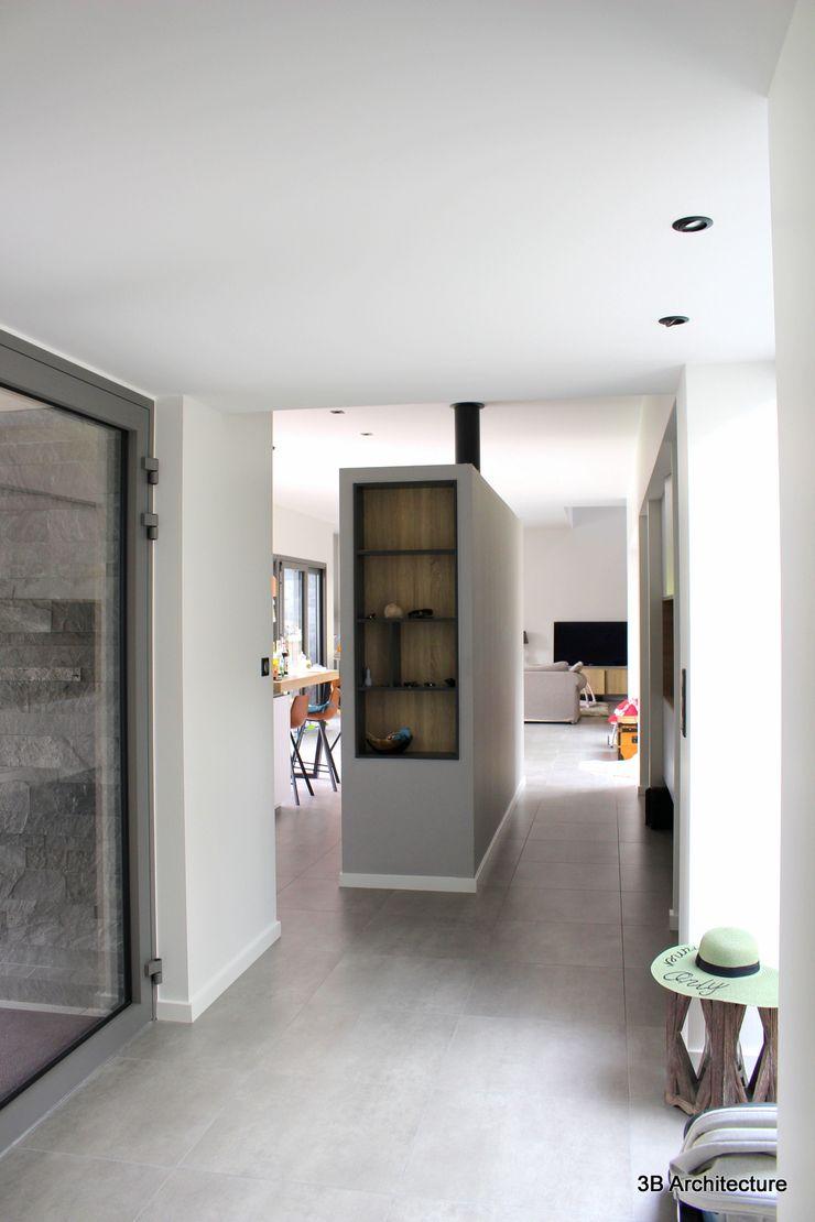 L'entrée s'ouvre finement sur l'espace de vie 3B Architecture Couloir, entrée, escaliers minimalistes Blanc