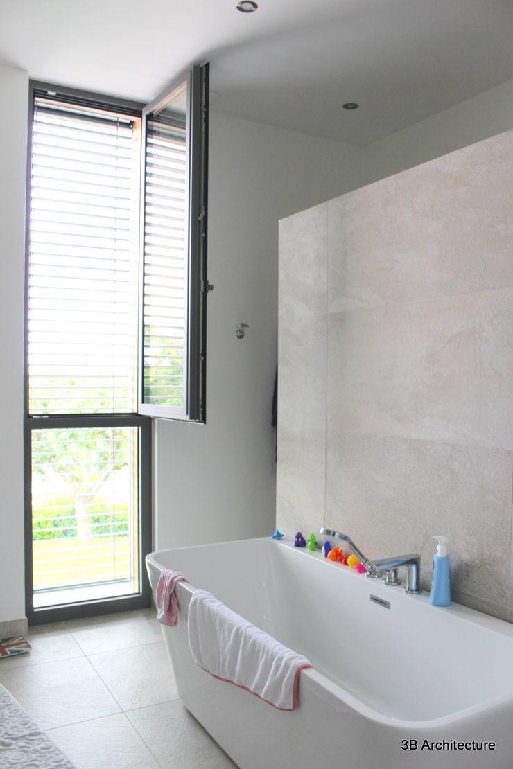 La salle de bains parentale, sa baignoire et sa douche cachée 3B Architecture Salle de bain minimaliste Bois Blanc