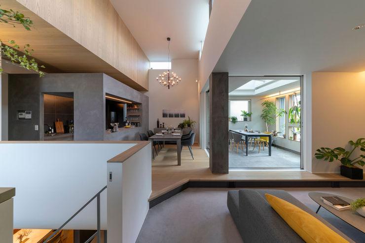 リビングからダイニングキッチン方向を見る タイコーアーキテクト モダンデザインの リビング 灰色
