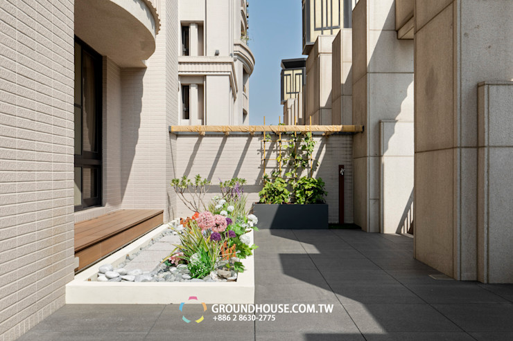 落地窗外還設置塑木坐檯讓人可以在此休憩 大地工房景觀公司 Tropical style balcony, veranda & terrace