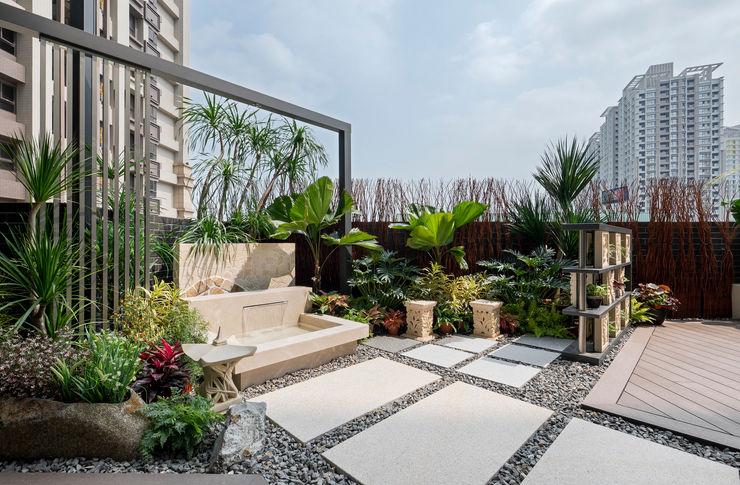 通往水池的步道鋪滿石頭,周圍還有許多熱帶植物 大地工房景觀公司 Tropical style balcony, veranda & terrace