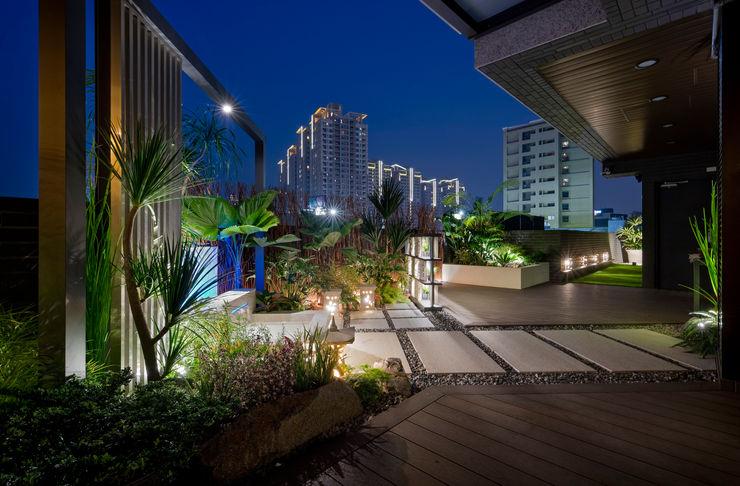 鄰棟的大樓燈光與露臺的熱帶氣息交織,讓人彷彿置身叢林都市 大地工房景觀公司 Tropical style balcony, veranda & terrace