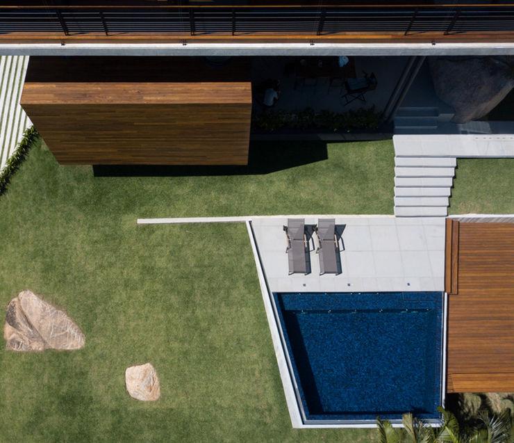 Vista del jardín y la piscina Alejandro Ortiz Arquitecto Piscinas de jardín Azulejos Azul