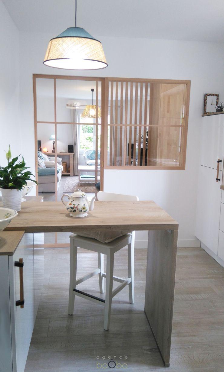 Cuisine avec vue sur salon Agence boÔbo Cuisine moderne Blanc