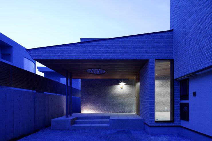 ルイスポールセンの銅の照明がタイルの質感を引き立たせる夜のエントランス イクスデザイン / iks design モダンスタイルの 玄関&廊下&階段 タイル ベージュ