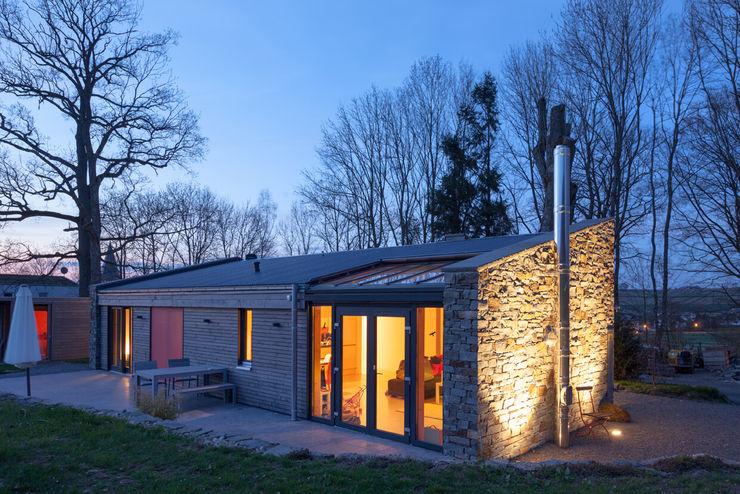 Fassadengestaltung und Außenbeleuchtung mit Bodeneinbaustrahlern plan.b lichtplanung Bungalow Holz
