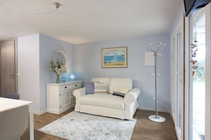 Area soggiorno con divano e cassettiera in stile country chic Arch. Sara Pizzo - Studio 1881 Soggiorno in stile mediterraneo Legno Bianco