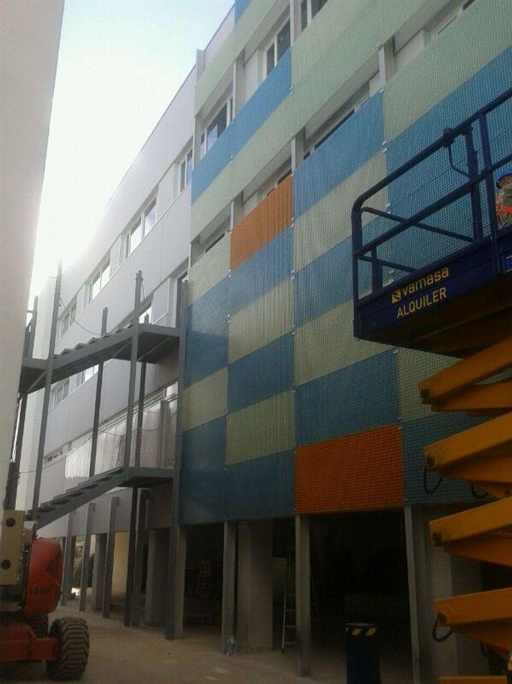 Fachada interior con revestimientos plásticos OCTANS AECO Casas de estilo industrial