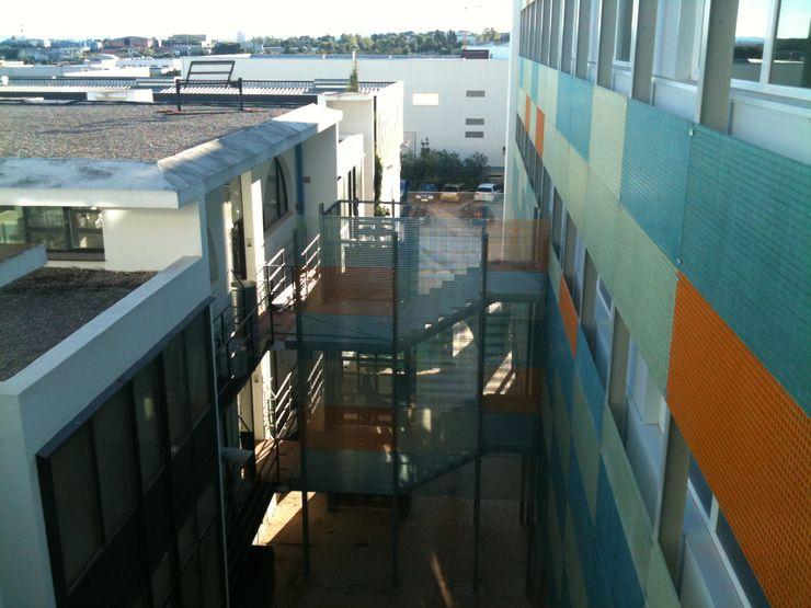 Otra vista exterior de la fachada interior con revestimientos plásticos OCTANS AECO Casas de estilo industrial