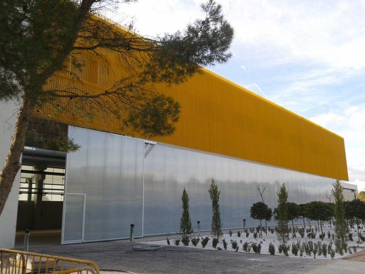 Vista exteriror de la fachada principal con revestimientos plásticos OCTANS AECO Casas de estilo industrial