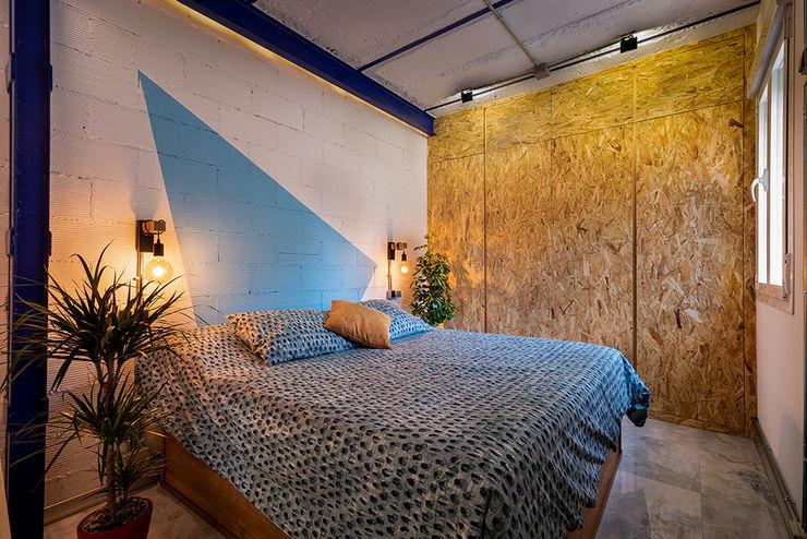 Dormitorio diferente en un apartamento de ciudad. OOIIO Arquitectura Dormitorios de estilo industrial Ladrillos Azul
