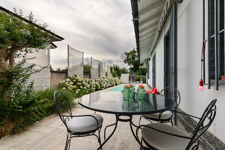 Tavolo da cocktail a bordo piscina Essestudioarch Giardino moderno