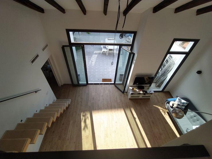 Vista interior: imagen del espacio a doble altura desde el piso superior OCTANS AECO Salones de estilo moderno