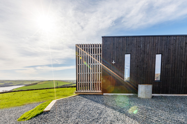 Hidden gate within wooden clad wall. Arco2 Architecture Ltd Wooden houses