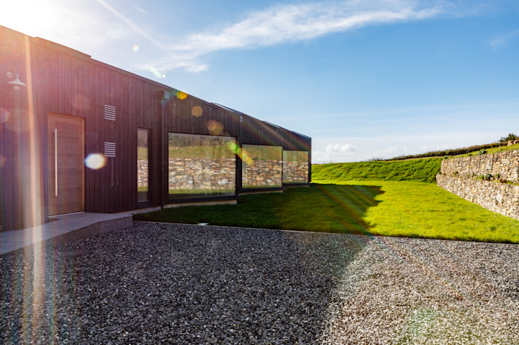 Simple garage and laid lawn surrounding impressive eco home Arco2 Architecture Ltd Front garden