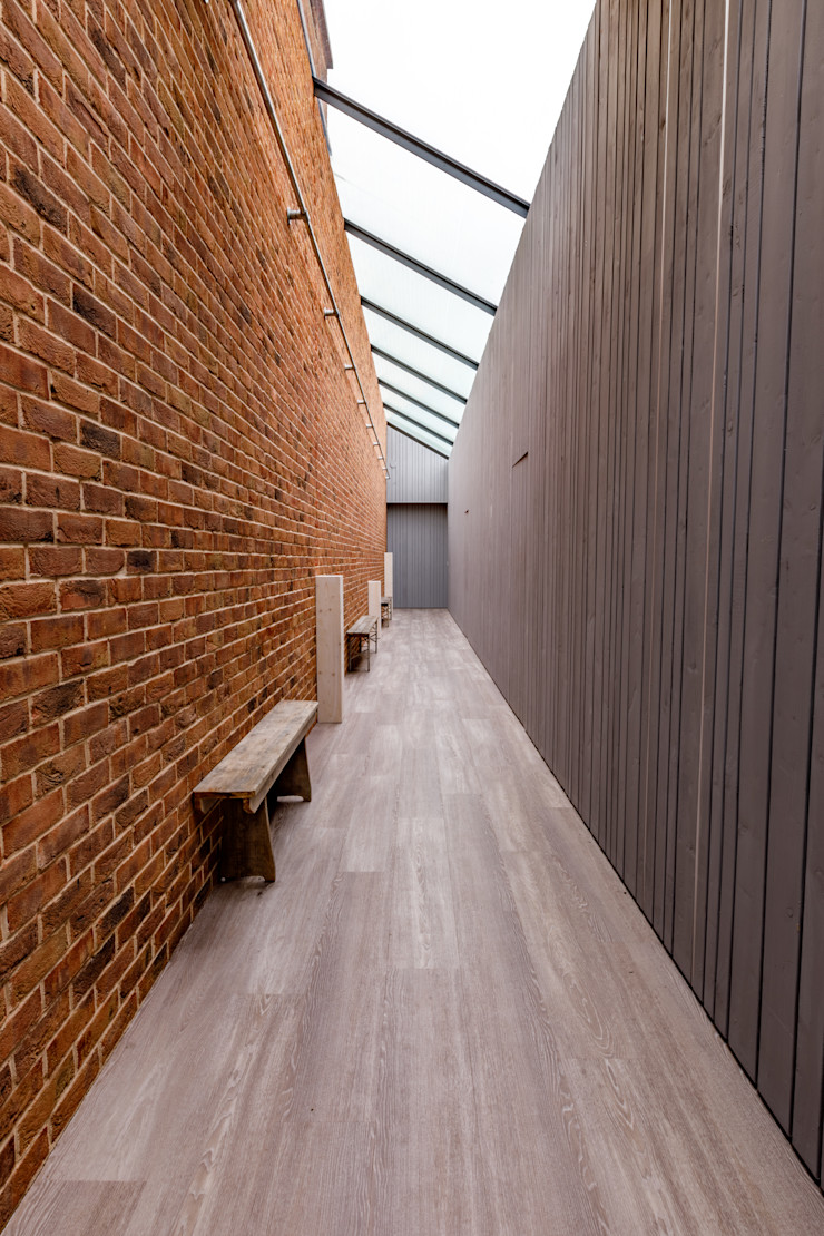 Internal Corridor with exposed red brick and wooden cladding. Arco2 Architecture Ltd Modern corridor, hallway & stairs