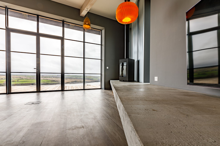 Polished Concrete Mantle, wood burner and Art Deco style full-height windows. Arco2 Architecture Ltd Modern living room