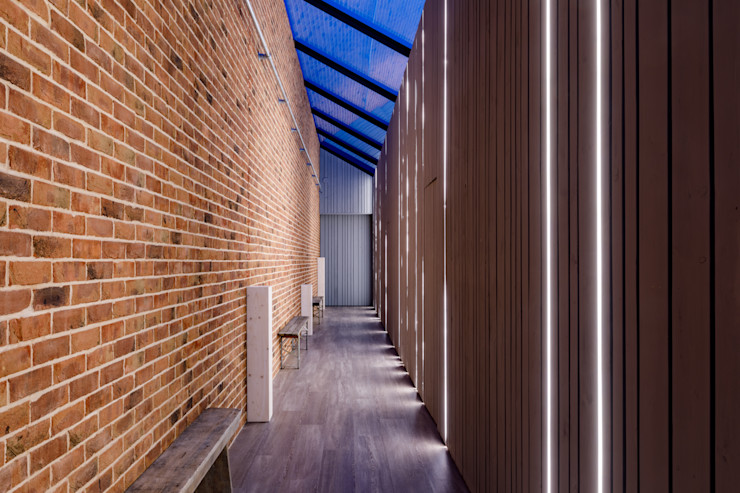 Internal Corridor with exposed red brick and wooden cladding and floor to ceiling lighting. Arco2 Architecture Ltd Modern corridor, hallway & stairs