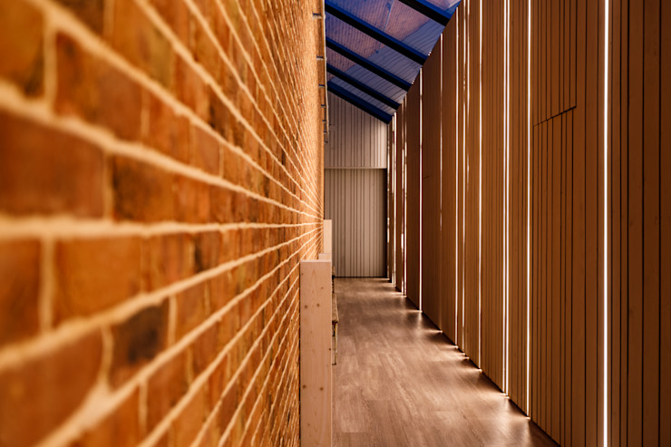 Red brick corridor and full height lighting. Arco2 Architecture Ltd Modern corridor, hallway & stairs