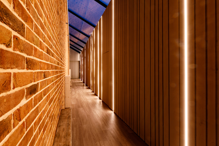 Painted wooden cladding and redbrick corridor with glass ceiling Arco2 Architecture Ltd Modern corridor, hallway & stairs