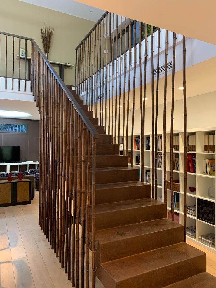 Escalera realizada en situ con zancas de hierro y chapa plegada para peldañeado, posteriormente oxidada también in situ, y barandilla artesanal de bambú natural Gomez-Ferrer arquitectos Escaleras Hierro/Acero Marrón