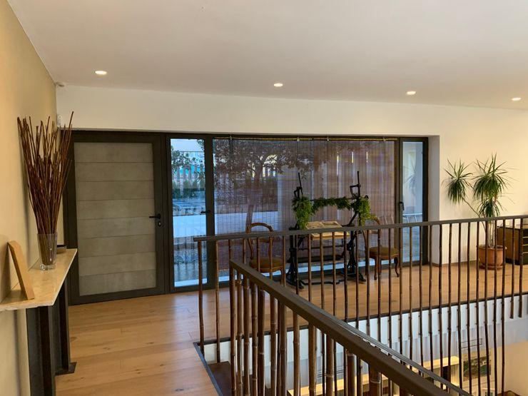 Hall de entrada con puerta aplacada en tablero de cemento y virutas tipo viroc. Gran cristalera con visión de la entrada desde la calle y aparcamiento Gomez-Ferrer arquitectos Pasillos, vestíbulos y escaleras modernos