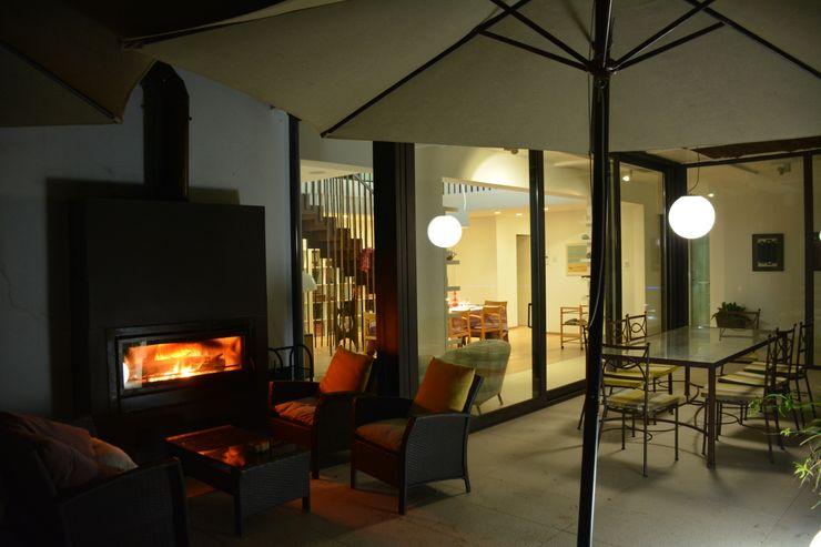 """Chimenea doble cara exterior-interior. Aprovechar las noches de casi todo el año alrededor de un """"fuego de campamento"""" Gomez-Ferrer arquitectos Balcones y terrazas modernos"""