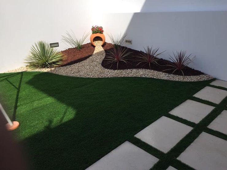 Jardim com relva sintética, pedra decorativa, fornecimento de plantas, patelas LOUSAJARDINS Jardins modernos