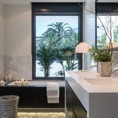 Relajante bañera con ventanal al jardín: Baños de estilo mediterráneo de Laura Yerpes Estudio de Interiorismo
