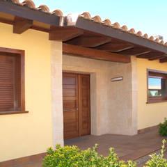 Portal de piedra con puerta de madera: Casas de estilo mediterráneo de RIBA MASSANELL S.L.
