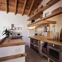 CASA EM FORMA DE ABRAÇO : Cozinhas rústicas por pedro quintela studio