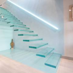 A single-flight cantilever staircase crafted in toughened, laminated glass: modern Corridor, hallway & stairs by Railing London Ltd