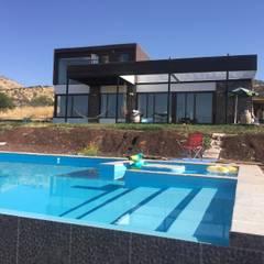 Casa en lo alto, piscina amplia mas abajo con bar incorporado: Piscinas de estilo translation missing: cl.style.piscinas.moderno por Arquiespacios